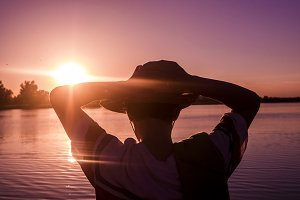 silhouette of young person in summer hat with hands raised behind the head looking at the purple sunset on the beach