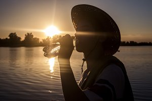 close up silhouette of young man in summer hat drinking bottled water against the sunset