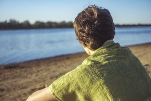 back view of man sitting on the beach in towel looking at water copy space