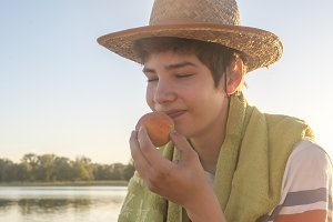 close up young man smelling peach fruit ready to bite it on the beach copy space