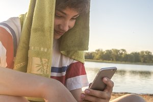 close up teenage boy with towel on the head in casual clothes using mobile phone