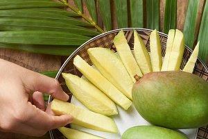 Hand taking slice of mango