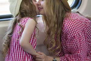 Attractive young woman kisses her cute daughter in front of the window in the train
