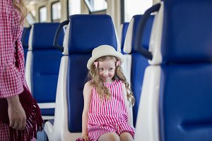 Happy little girl sitting on chair at speed train