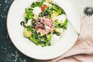 Fresh green summer salad with artichokes over wooden painted background