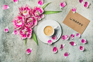 Cup of coffee surrounded with pink tulip flowers, marble background