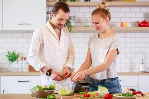Image of loving couple cooking vegetables in kitchen