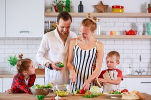 Photo of young mother and father with son and daughter preparing breakfast