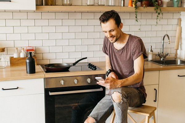 People Stock Photos: Super duper stock images  - Portrait of brunet man with frying pan in his hands talking on phone in kitchen