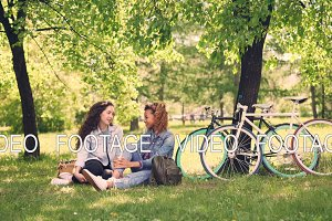 Smiling girls are having conversation in park sitting on lawn and sharing news after riding bikes, young women are happy and relaxed. Mixed race friendship and nature concept.