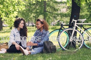 Cheerful young women Caucasian and African American are chatting in park while resting after riding bikes in beautiful green park. Girls are careless and happy.