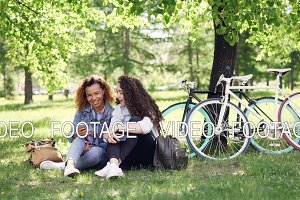 Happy African American woman is showing her Caucasian friend her smartphone screen, girls are looking at it, talking and laughing. Bikes, grass and trees are visible.