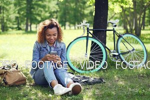 Happy African American girl is using smartphone touching screen and smiling while resting in park after riding bike. Modern bag and bicycle are visible.