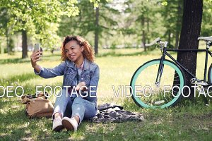 Pretty African American girl is making video call with smartphone, she is looking at screen, talking and waving hand. Beautiful park with grass and trees is visible.