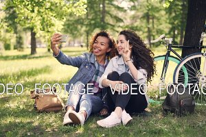 Pretty girls friends are taking selfie in park sitting on lawn with bicycles in background. Mixed race friendship, modern technology and cheerful people concept.