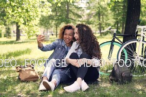 Cheerful women are looking at smartphone screen and laughing then taking selfie together posing for camera sitting on grass in park. Bicycles and backpacks are visible.