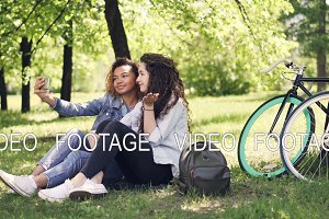 Young woman and her African American friend are taking selfie, posing and having fun sitting on lawn in park. Warm sunny day, beautiful nature and modern lifestyle concept.