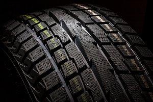 SUV winter tyre on black background,