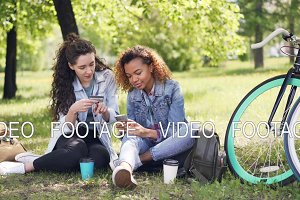 Two young women are paying with card using smartphone sitting in park on grass holding credit card and phone then doing high five and laughing. Online payment concept.