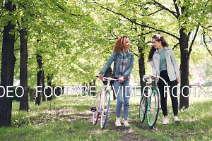 Sporty young women are walking with bicycles in park, smiling and talking. Beautiful nature, interesting conversation and cheerful people concept.