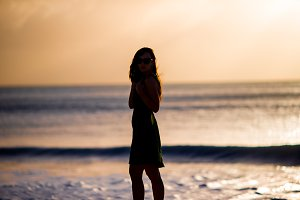 Beautiful woman on white beach at sunset.