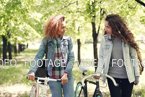 Dolly shot of cheerful girls friends walking in park with bikes relaxing after riding bicycles and socializing. Multiethnic friendship, hobby and active lifestyle concept.