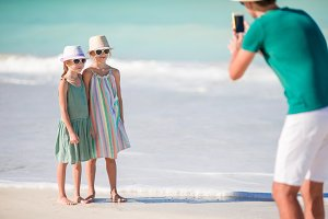 Man taking a photo of his kids on the beach