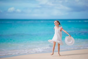 Beautiful little girl in dress at beach having fun.