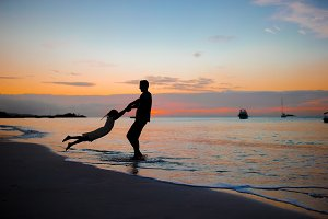 Little girl and happy father silhouette in the sunset at the beach