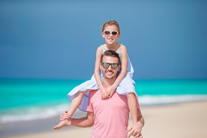 Little girl and happy dad having fun during beach vacation