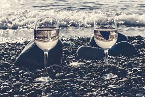 Two glasses of white wine by sea