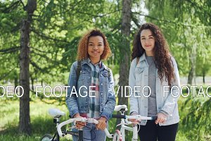 Portrait of happy young women Caucasian and African American standing together in nice green park, holding bikes, looking at camera and smiling. People and nature concept.