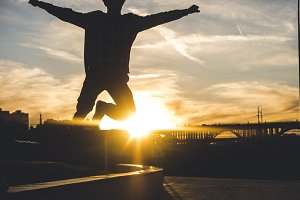 silhouette of young man jumping in the city against the sunset