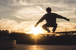 young teenage boy flying in the city against the sky sunset