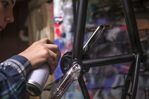 close up hand of mechanic painting the bmx bicycle frame