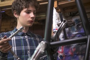 portrait of young man repairing the bmx bicycle holding instruments in garage
