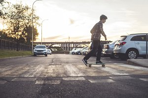 young hipster boy crossing the street riding the skateboard in the urban city