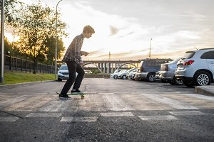 young active teenage boy riding the skateboard on the crosswalk in urban city