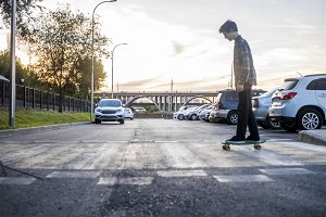 portrait of man riding the skateboard crossing the street motion blur