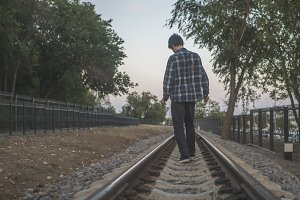 young alone man walking on the railroad track between the trees