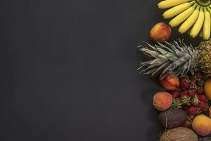 tropical pineapple mini bananas oranges coconut and other delicious fruits of dark background copy space
