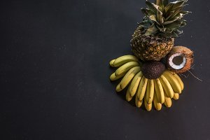 overhead copy space pineapple mini bananas and coconut exotic fruit concept