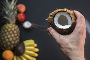 hand holding coconut with tropical fruits on black background summer holidays concept