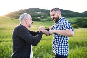An adult hipster son with senior father making fist bump in nature at sunset.