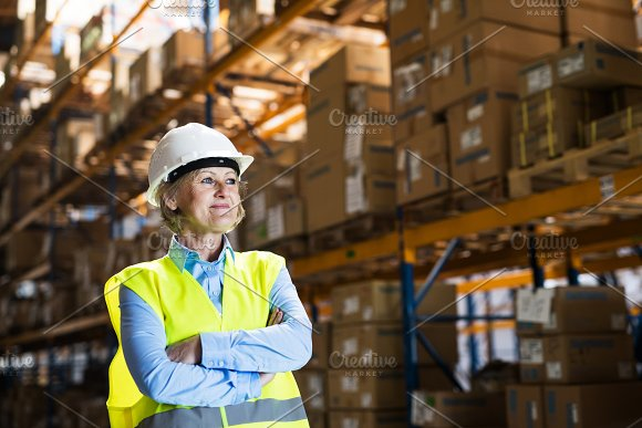 Senior woman manager or supervisor standing in a warehouse, arms crossed. in Graphics