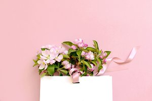White gift bag and spring flowers