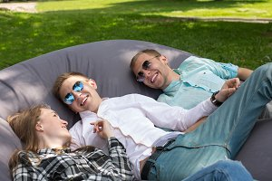 Three happy laughing friends chilling outdoors in the park on a