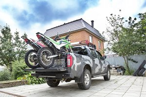 Two dirt bike motorcycles on the back of the camo truck on the d