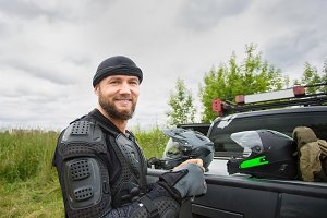 Happy smiling young man outdoors wearing motorcycle gear and loo