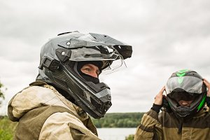 Two men outdoors wearing motorcycle helmets and uniforms.